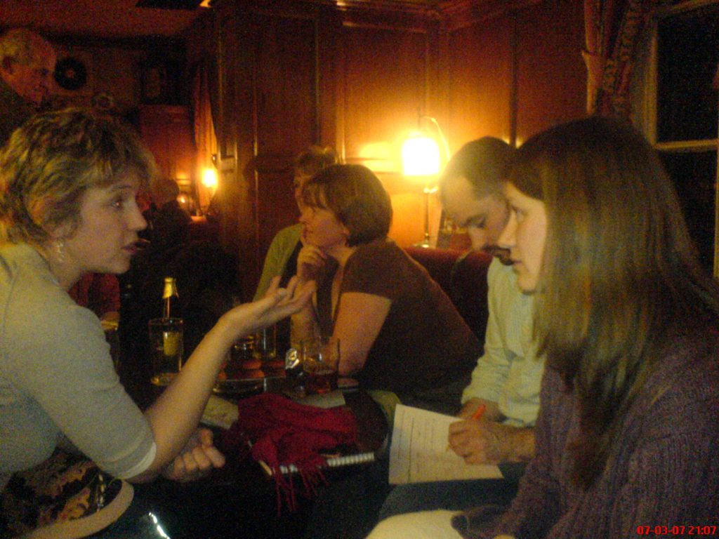Group of people talking in pub in evening