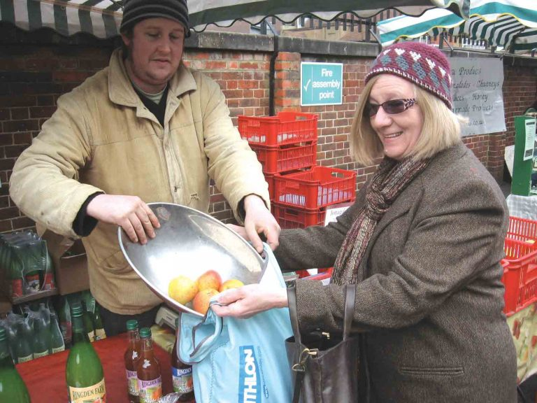 Woman buying apples from market stall