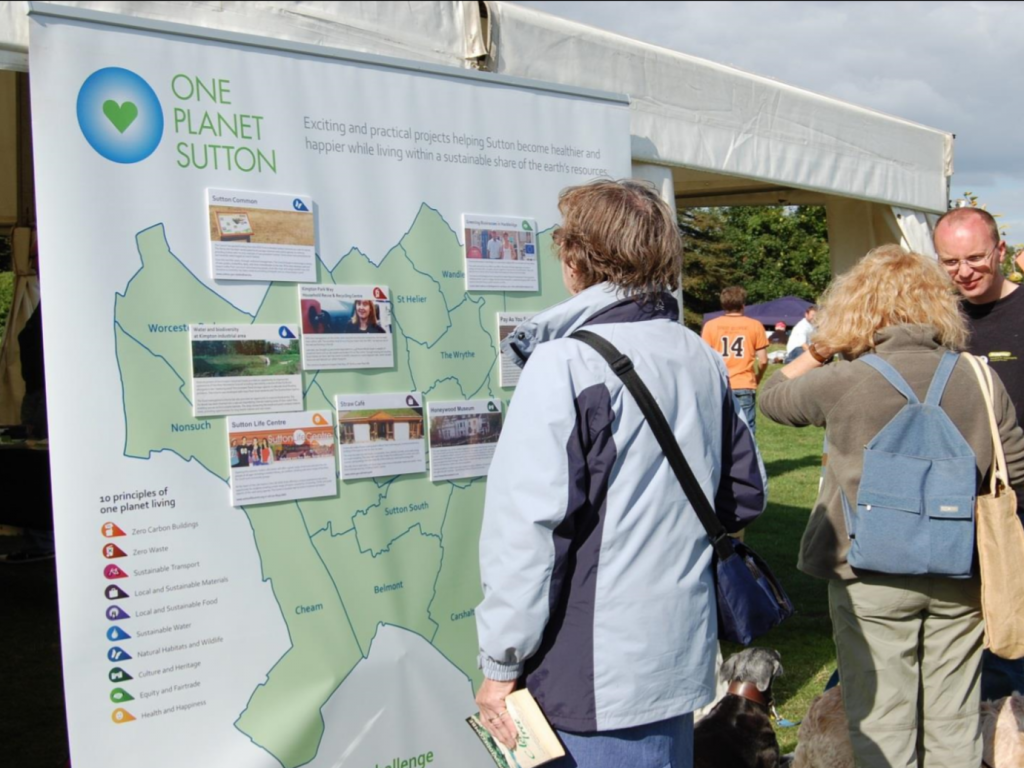 People at an outdoor fair with large borough map display